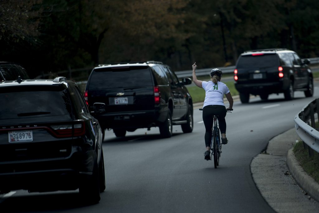 TOPSHOT - A woman on a bike gestures with her middle finger as a motorcade with US President Donald Trump departs Trump National Golf Course October 28, 2017 in Sterling, Virginia. / AFP PHOTO / Brendan Smialowski (Photo credit should read BRENDAN SMIALOWSKI/AFP/Getty Images)